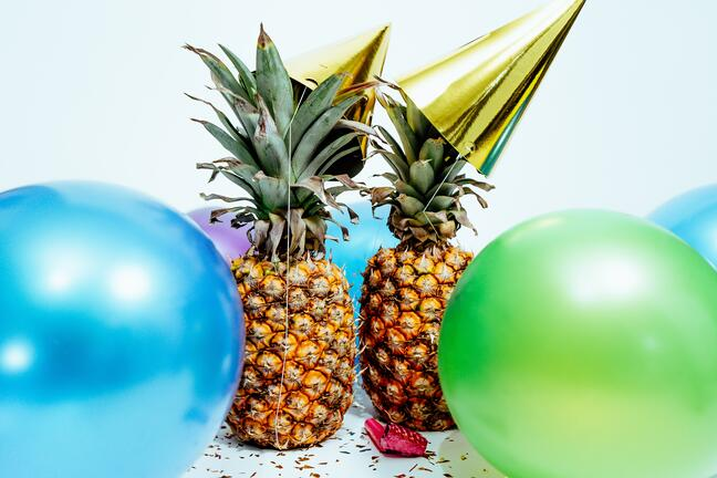 two pineapples wearing party hats with balloons