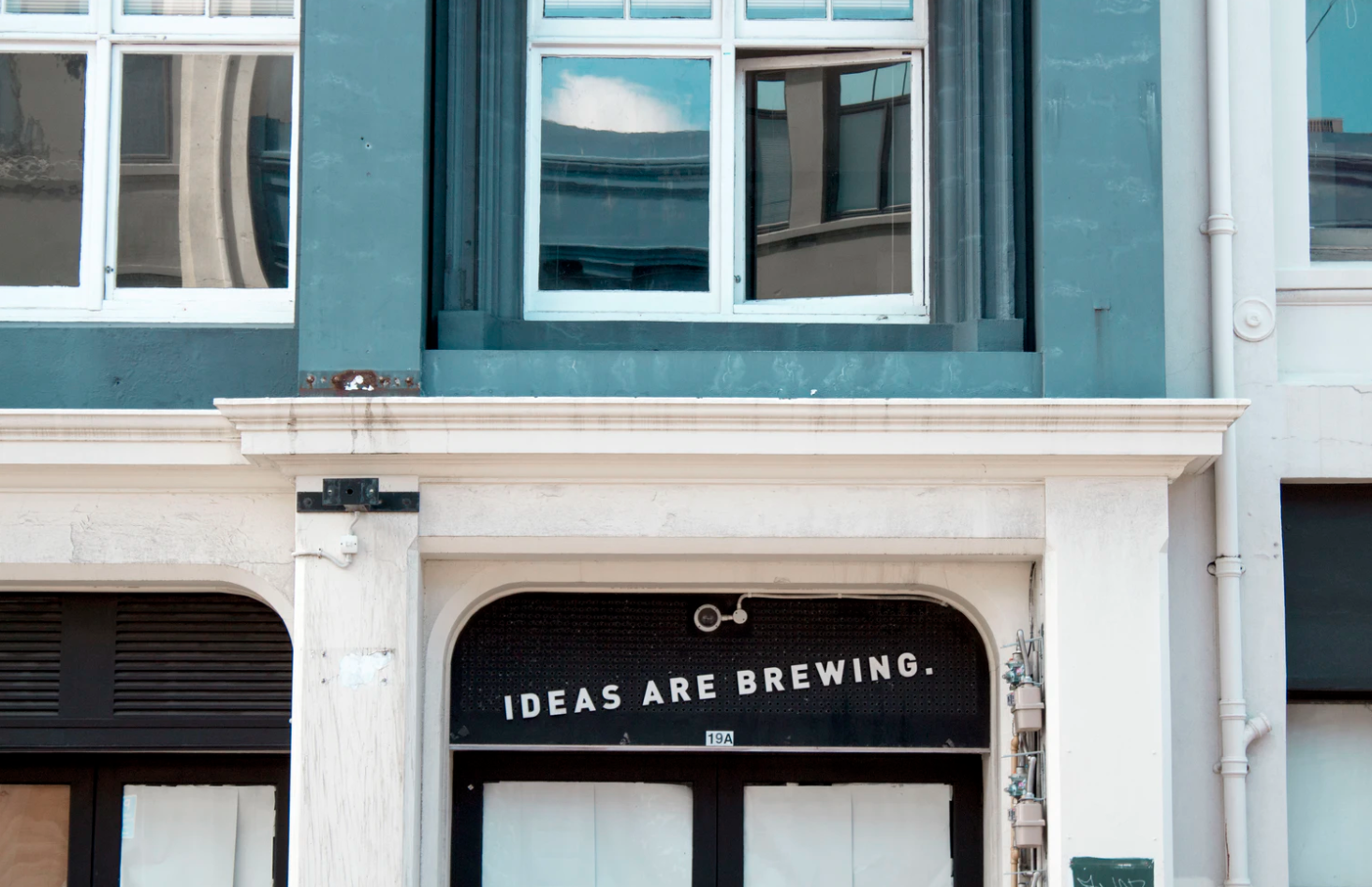 """front of a building with a sign on a door that reads """"ideas are brewing"""""""